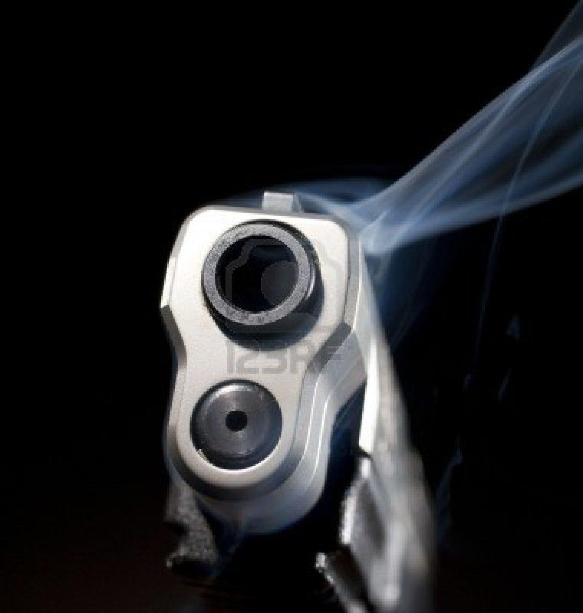 Smoking-gun-that-is-still-releasing-blue-smoke-on-black