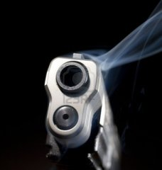 Smoking-gun-that-is-still-releasing-blue-smoke-on-black